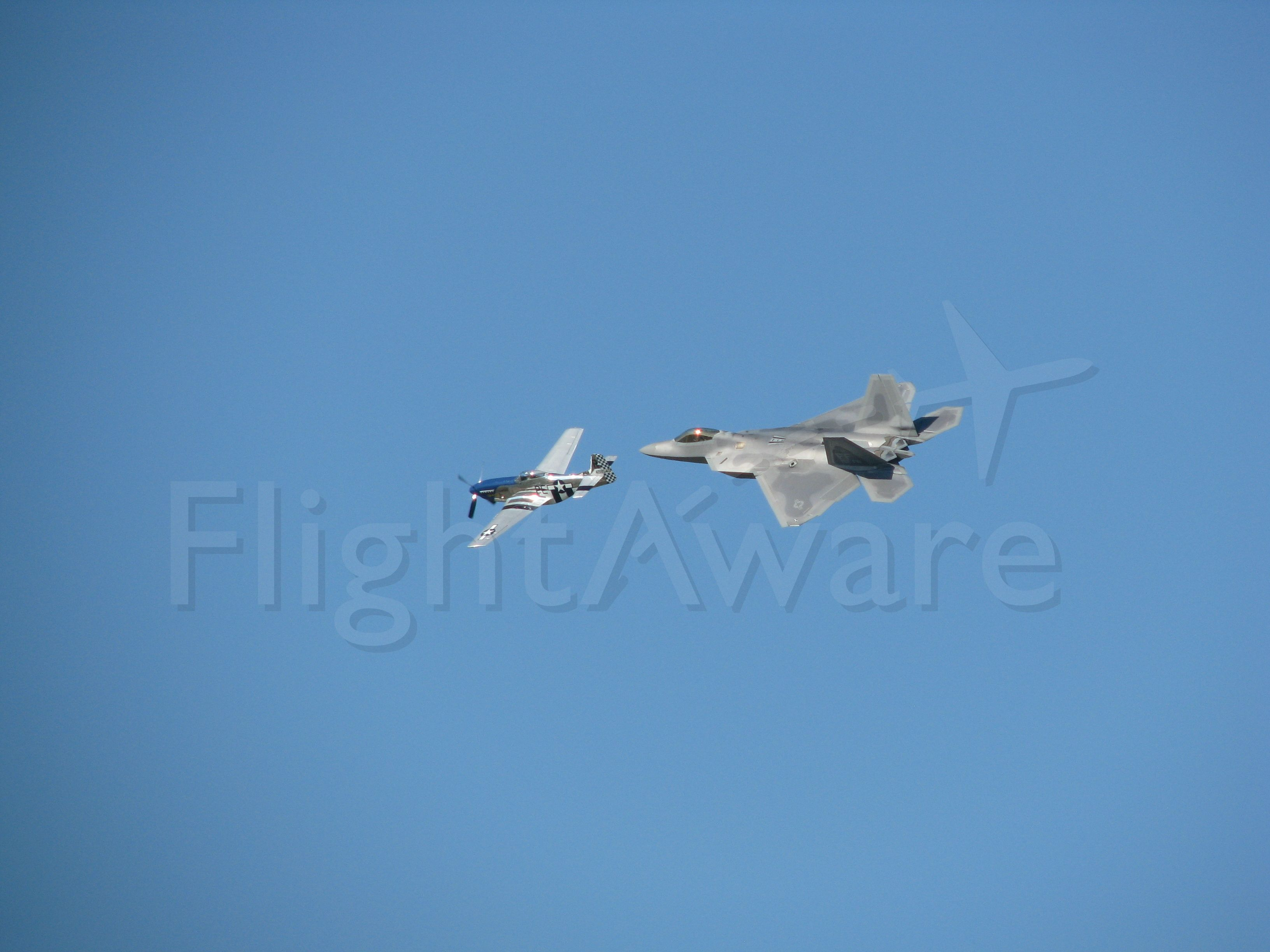 — — - P-51 Mustang and F-22 Raptor fly formation at Oshkosh 2008.