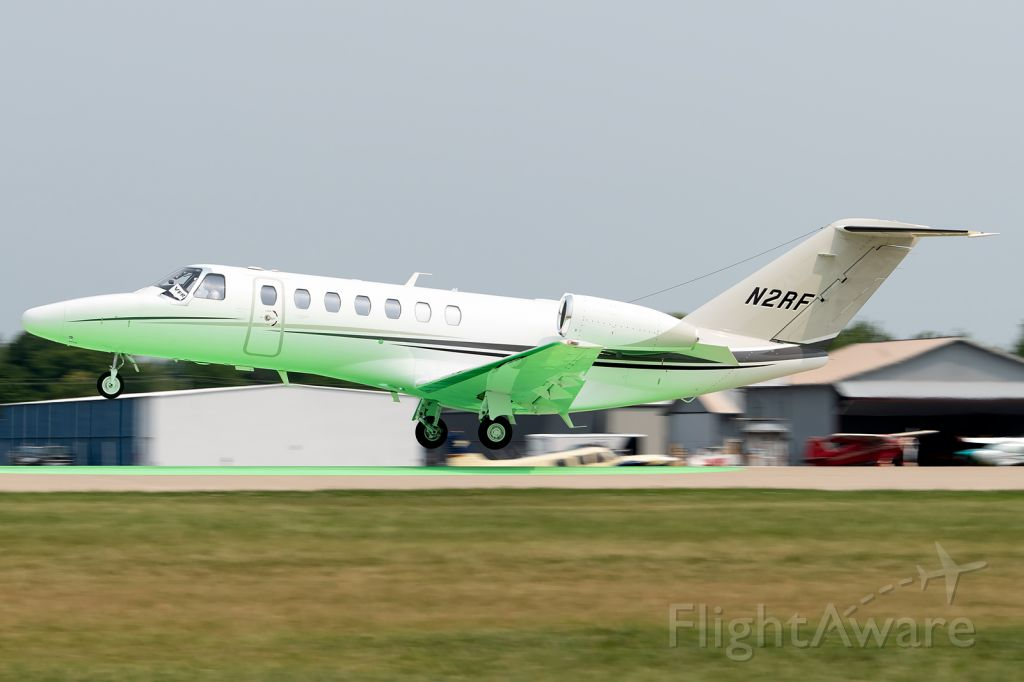 Cessna Citation CJ3 (N2RF) - The green dot on runway 27 reflects on the belly of this nice looking Citation as it departs to escape incoming severe weather.
