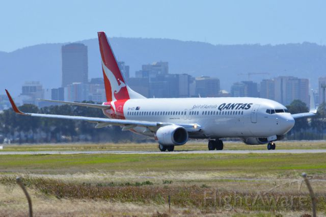 Boeing 737-800 (VH-VZY) - On taxiway heading for take-off on runway 05. Part of the Adelaide city skyline can be seen in the background. Thursday 6th March 2014.